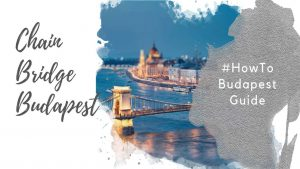 "Feature image for an article about the Budapest Chain Bridge. A watercolor foreground has the text ""Chain Bridge Budapest"" and ""#howtobudapestguide"". The background image shows a segment of the Szechenyi Chain Bidge over the Danube, and the Hungarian Parliament Building, at dusk against a blue sky. The bridge and parliament building are lit up."