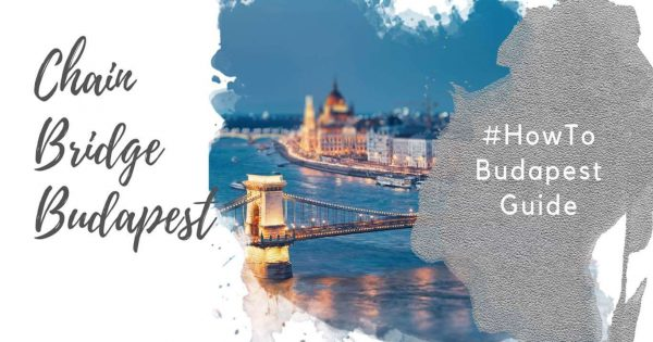 """Feature image for an article about the Budapest Chain Bridge. A watercolor foreground has the text """"Chain Bridge Budapest"""" and """"#howtobudapestguide"""". The background image shows a segment of the Szechenyi Chain Bidge over the Danube, and the Hungarian Parliament Building, at dusk against a blue sky. The bridge and parliament building are lit up."""