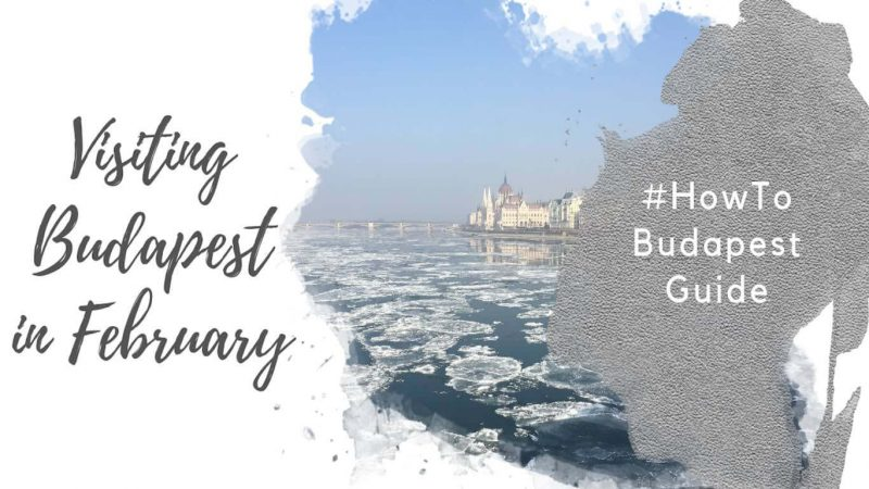 "Feature image for an article about Visiting Budapest in February. A watercolor foreground has the text ""Visiting Budapest in February"" and ""#howtobudapest"". The background image shows the Danube river in winter, with ice on it. You can see the Hungarian parliament building in the distance."