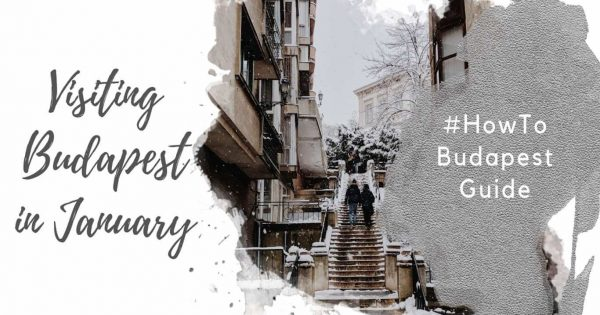 """Feature image for an article about Visiting Budapest in January. A watercolor foreground has the text """"Visiting Budapest in January"""" and """"#howtobudapest"""". The background image shows two people climbing outdoor stairs in Buda, near Budapest Castle. There is snow on the ground and in the trees and it is winter."""