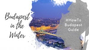 "Feature image for an article about Visiting Budapest in Winter. A watercolor foreground has the text ""Budapest in the Winter"" and ""#howtobudapest"". The background image shows the a panorama of the Pest skyline and Liberty Bridge at dusk, against a blue sky. The Danube has ice flows floating on it."