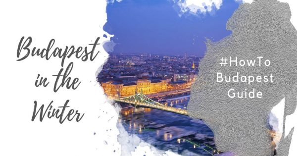 """Feature image for an article about Visiting Budapest in Winter. A watercolor foreground has the text """"Budapest in the Winter"""" and """"#howtobudapest"""". The background image shows the a panorama of the Pest skyline and Liberty Bridge at dusk, against a blue sky. The Danube has ice flows floating on it."""